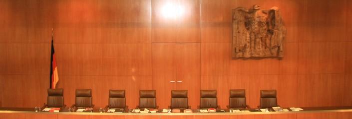 Die Stühle der Verfassungsrichter im Sitzungssaal des Bundesverfassungsgericht. An der Wand ist die bekannte Schnitzerei des Bundesadlers zu sehen.