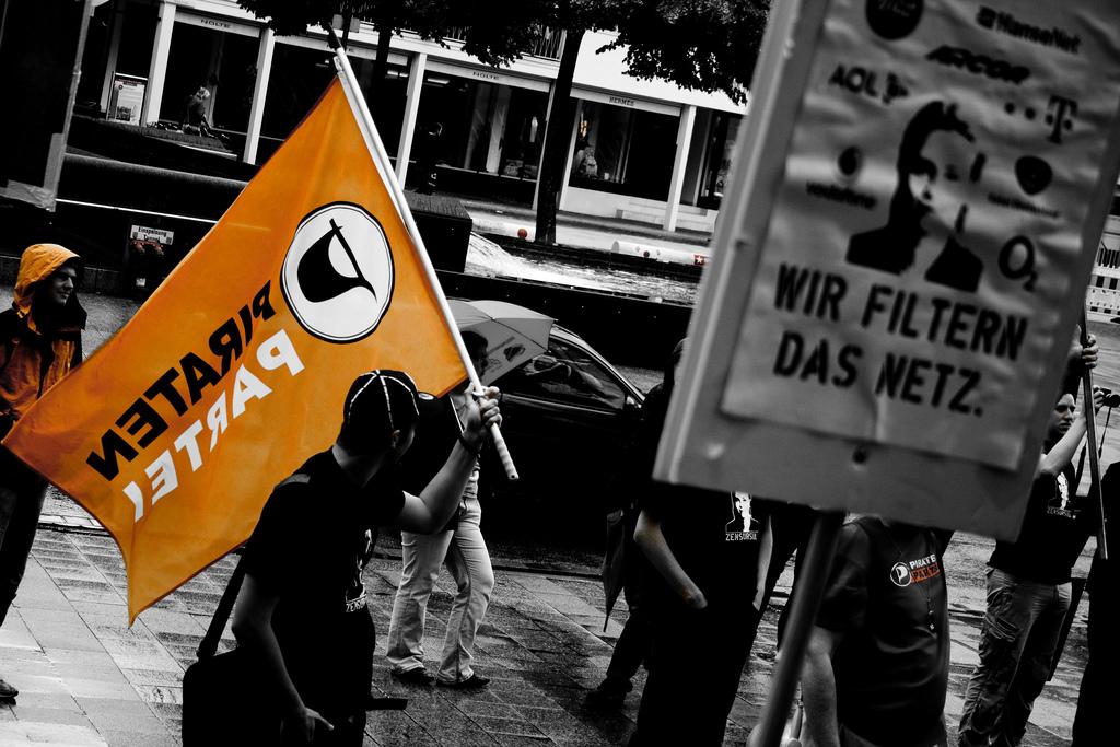 Demonstranten mit Piratenpartei-Flagge; im Vordergrund ein Zensursula-Poster